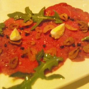 Beef Carpaccio hard boiled quail egg, baby arugula, garlic chips, fried capers and pequin chili oil